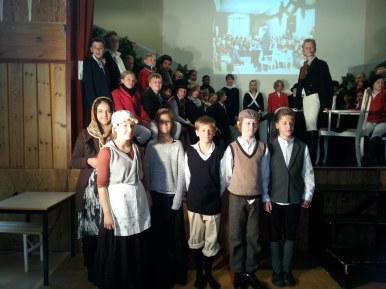 Fra ptøvene til 1814 - dramaet på Kvaleberget skole, foran podiet står tjenestefolkene og bak ser vi Eidsvoldsmennene. podiet st