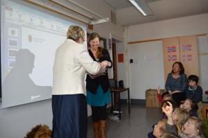Magnhild Meltveit Kleppa overrekker bøkene om Mina og løven til klasselærer Susanne Rodvelt Haugland. Foto B. Møen